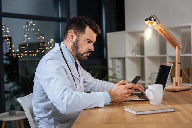 Era da tecnologia. médico bonito e inteligente olhando para a tela do smartphone e usando um laptop enquanto trabalhava no escritório