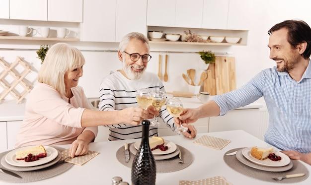 Erguendo nossas taças de felicidade. agradável casal de idosos, animado e fofo, jantando e comemorando o feriado com o filho maduro, levantando taças de champanhe