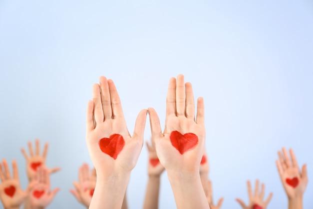 Erguido nas mãos com corações desenhados nas palmas das mãos contra a luz.