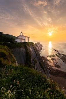 Ermitage de san telmo no topo do penhasco da praia de itzurun em zumaia, país basco.