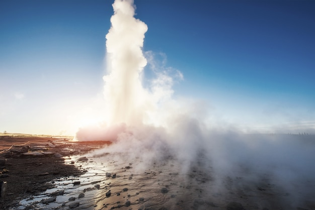 Erupção do geyser de strokkur na islândia. cores fantásticas brilham através do vapor. belas nuvens cor de rosa em um céu azul