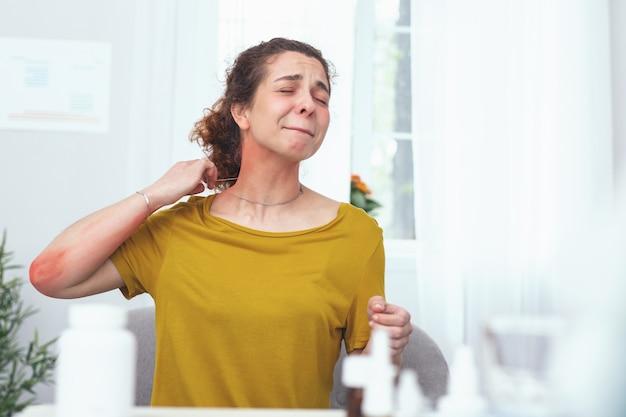 Erupção no pescoço. mulher jovem com aparência infeliz e dolorida, sofrendo de dor no pescoço e erupções alérgicas enquanto tentava tirar o colar e aplicar um medicamento