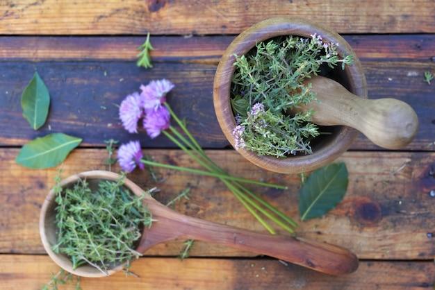 Erva aromática em uma colher de pau e almofariz sobre uma mesa de madeira