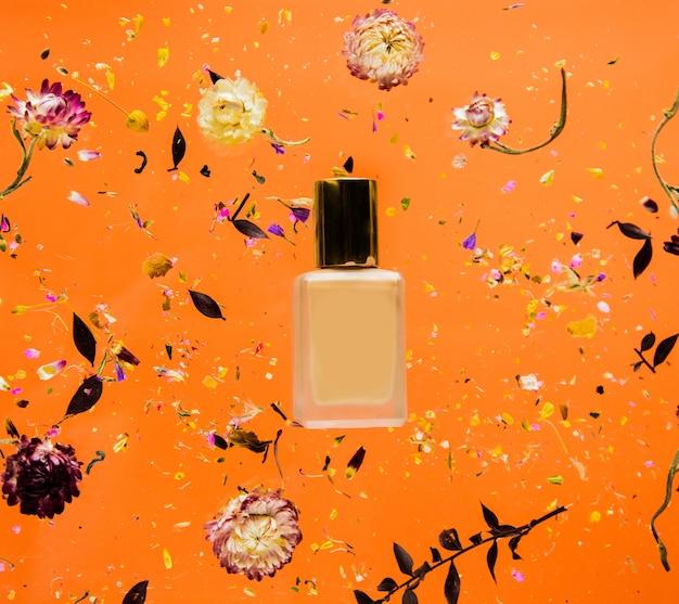 Erva bellis seca com frasco de fundação em fundo laranja isolado. sem sombras