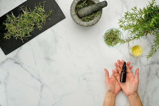Erva de alecrim e óleos essenciais em vista de mesa de mármore
