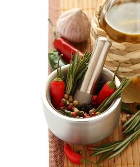 Erva de alecrim fresco e pimenta vermelha em almofariz de metal com pilão, azeite e alho chinês