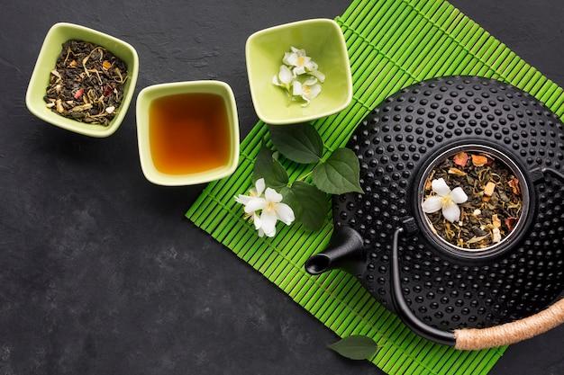 Erva de chá seco com flor de jasmim branco no plano de fundo texturizado