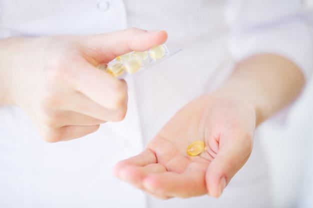 Erva de medicina. comprimidos ervais à disposição, palma, dedos com a planta médica saudável. suplemento vitamínico para cuidados, medicação