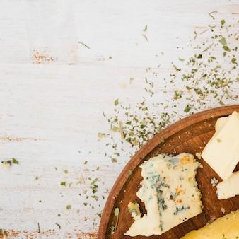 Ervas com queijo na bandeja de madeira sobre a mesa branca