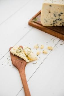 Ervas com queijo na espátula sobre a mesa de madeira branca