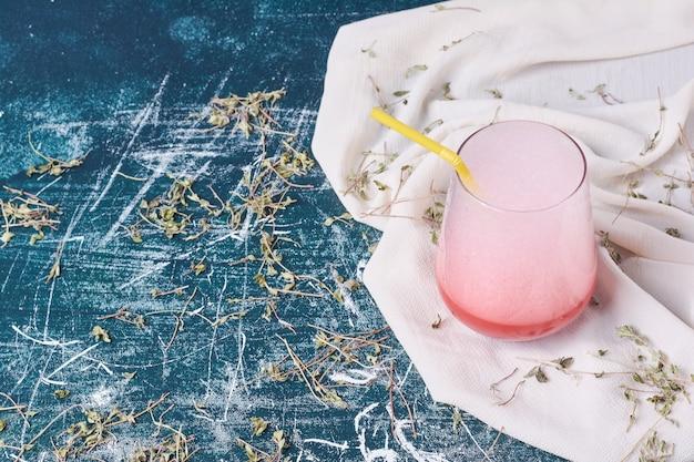 Ervas com um copo de bebida em azul.