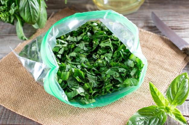 Ervas congeladas (manjericão) em um saco plástico. vegetais congelados. conceito de comida congelada