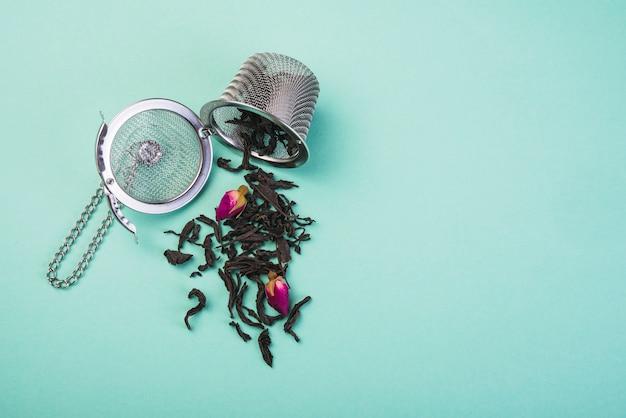Ervas de chá secas soltas derramadas do coador de chá contra o pano de fundo colorido