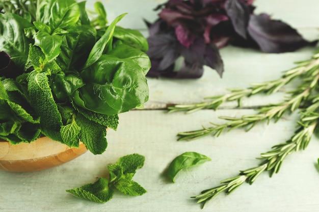 Ervas de manjericão, alecrim e hortelã na mesa de madeira