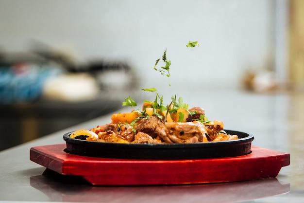 Ervas decorativas em um prato cozido com carne e vegetais