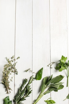 Ervas diferentes na mesa de madeira branca, vista superior