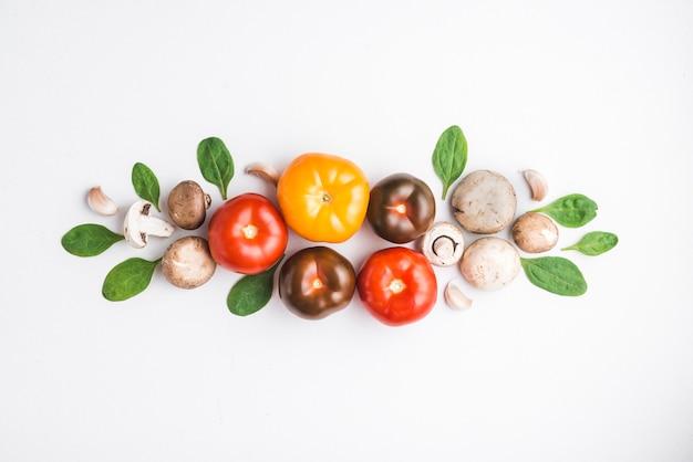 Ervas e cogumelos perto de tomates