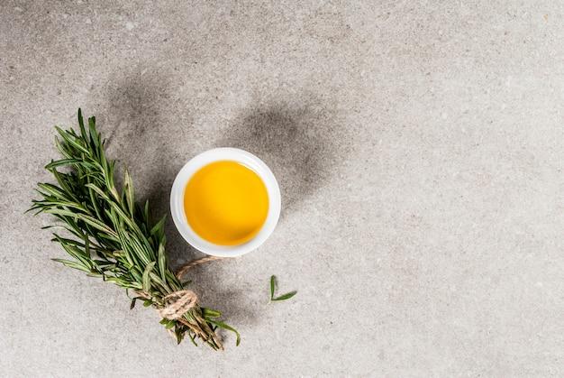 Ervas e especiarias. alecrim e azeite de oliva em background de pedra cinza