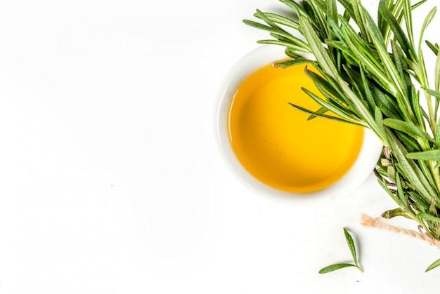 Ervas e especiarias. alecrim e azeite de oliva no fundo branco, para