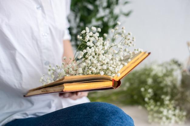 Ervas e gipsofila na mesa de madeira com livro