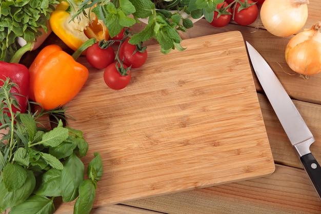 Ervas e legumes com uma tábua de cortar