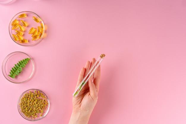 Ervas e suplementos alimentares à base de plantas, vista superior em fundo rosa