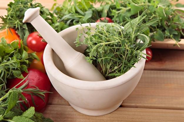 Ervas frescas com um almofariz e pilão