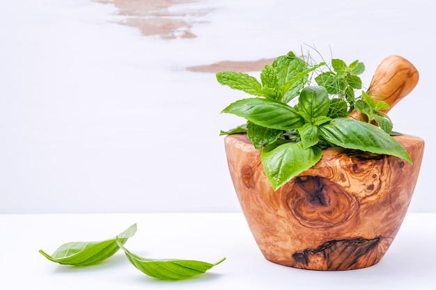 Ervas frescas de medicina alternativa no conjunto de argamassa de madeira sobre fundo branco de madeira