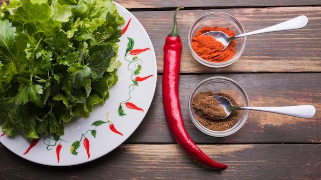 Ervas frescas na placa perto de pimenta em taças e pimentão