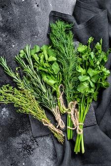 Ervas frescas orgânicas coentro, alecrim, tomilho, endro, salsa. fundo preto. vista do topo