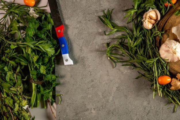 Ervas frescas top tarragom salsa e alho em cinza com espaço de cópia
