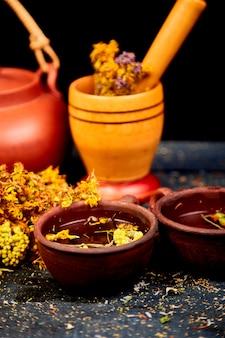 Ervas medicinais na mesa de madeira preta, fitoterapia