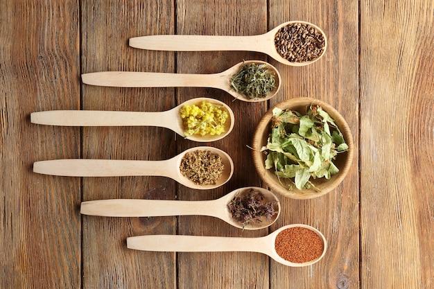 Ervas medicinais secas e sementes em colheres na mesa de madeira