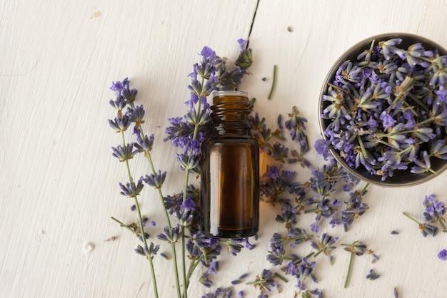 Ervas provençais. óleo de lavanda em uma garrafa de vidro. uma tigela com flores em branco. postura plana