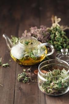 Ervas secas na mesa de madeira e chaleira para chá