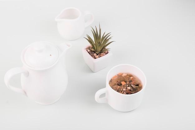 Ervas secas no chá perto de louças em pano de fundo branco