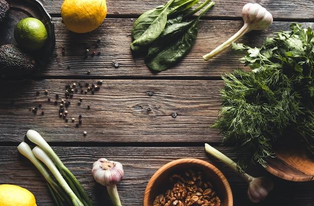 Ervas verdes culinárias, espinafre, endro, salsa e abacate em uma caixa de madeira isolada em uma superfície de madeira