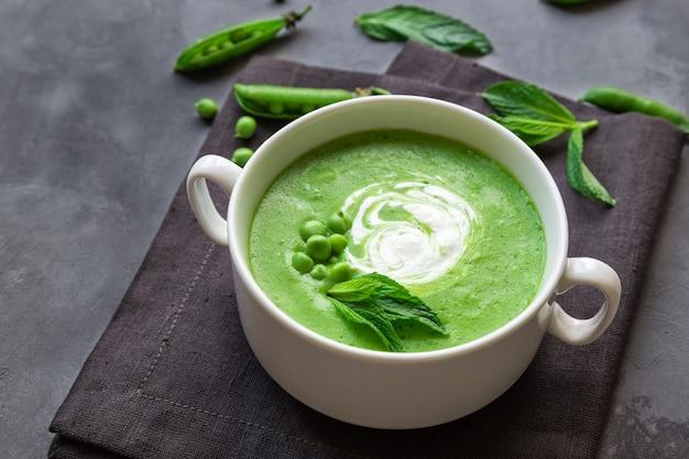 Ervilha verde e sopa de hortelã em uma tigela sobre concreto cinza.