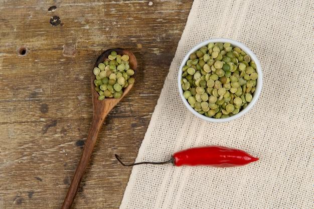Ervilha verde seca crua em vidro na mesa de madeira perto de pimenta