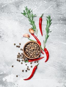 Ervilhas em uma tigela com fatias de pimenta vermelha, alecrim e alho. em fundo rústico