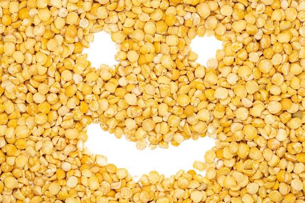 Ervilhas secadas da separação amarela, cara engraçada do sorriso, fim acima, macro, vista superior.