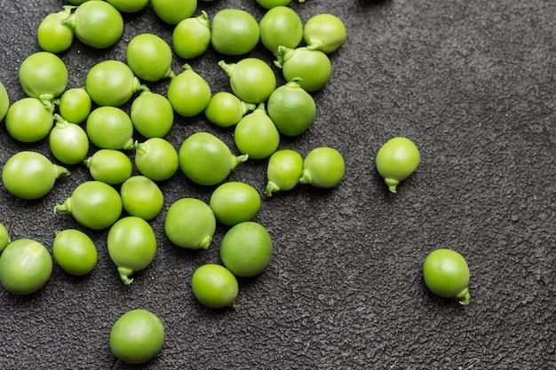 Ervilhas verdes descascadas na mesa. fundo preto. postura plana