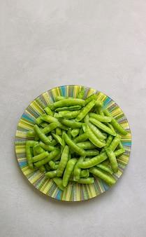 Ervilhas verdes em um prato, cinza