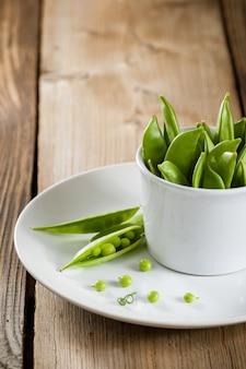 Ervilhas verdes em vagens em chapa branca na mesa de madeira