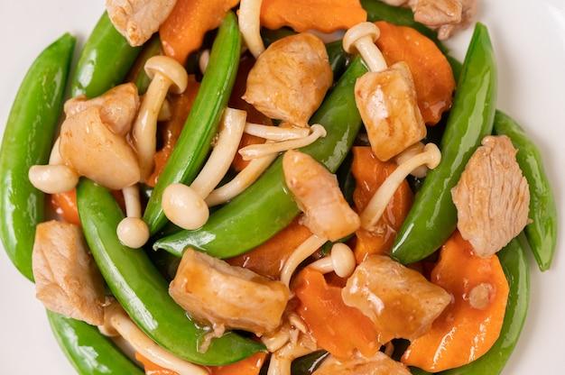 Ervilhas verdes fritas com carne de porco, cogumelos e cenouras em um prato branco