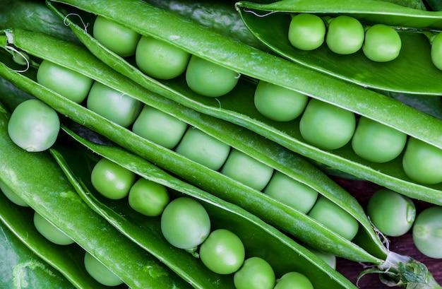 Ervilhas verdes, macias, frescas e cruas. close-up e vista superior. aparência rústica.