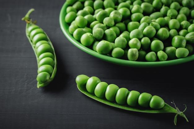 Ervilhas verdes maduras deliciosas que encontram-se em uma tabela de madeira.
