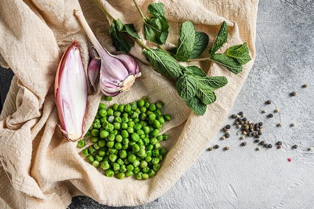 Ervilhas verdes orgânicas para ervilhas de cogumelos e ingredientes hortelã cebolinha chalé comida foto sobre fundo de pedra cinza e pano vista superior