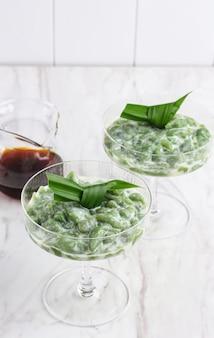 Es cendol ou dawet é a sobremesa congelada tradicional da indonésia, feita com farinha de arroz, açúcar de palma, leite de coco e folha de pandanus servida em vidro. popular durante o jejum do ramadã