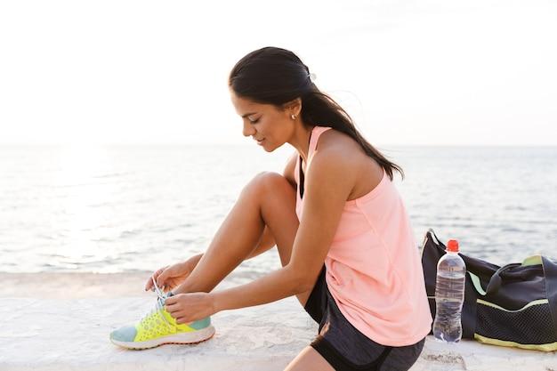 Esbelta esportista europeia usando um agasalho de agachamento e amarrando o cadarço do tênis no calçadão durante um treino à beira-mar